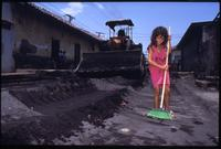 A young girl sweeps ash and debris off the street while a bulldozer clears behind her after the eruption of the Cerro Negro volcano