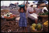 A young girl stands in a market with a bowl of fruit atop her head, Managua, Nicaragua