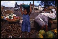 A young girl stands near a pile of cassava in a market with a bowl of fruit atop her head, Managua, Nicaragua