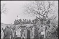 Alternate view of students on top of a painted bus, gathered to protest Nixon's inauguration and the Vietnam War, 19 January 1969