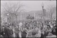Alternate view of the crowd of students assembled to protest Nixon's inauguration and the Vietnam War filling the streets at Independence Ave and 6th St SW and the area around Seaton Section Park, 19 January 1969