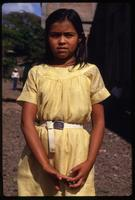 A young girl wearing a yellow dress for a Good Friday procession, Managua, Nicaragua