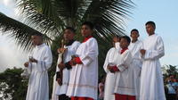 Alter boys stand with thurible and crucifix outside church on Baptism Day in El Plátano, Panama