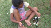 A young girl sits outside preparing to paint her nails, Panama Este, Panama
