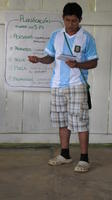 Alternate view of a man wearing a jersey addressing others at an agribusiness seminar in Bocas del Toro, Panama