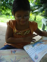 A young girl reads a children's book wearing Rachel Teter's glasses, El Plátano, Panama