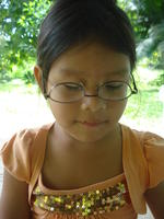 A young girl wearing Rachel Teter's glasses upside down, El Plátano, Panama
