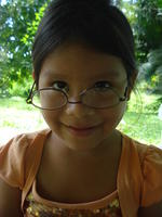 A young girl wears Rachel Teter's glasses upside down, El Plátano, Panama