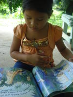 A young girl reads a children's book, El Plátano, Panama