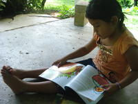 A young girl sits on a concrete porch reading a children's book while wearing Rachel Teter's glasses, El Plátano, Panama