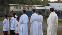 Alter boys and priest walk in procession towards road on Baptism Day, El Plátano, Panama
