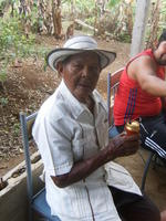 Abuelo Santo sitting in chair with beverage celebrating his 93rd birthday in El Plátano, Panama