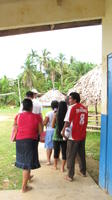 Adults and children exit class toward bamboo huts in Bocas del Toro, Panama
