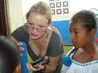 Young girl watches as Rachel Teter applies makeup to a girl for the patronage festival in El Plátano, Panama