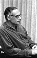 Alternate portrait of seated Herb Striner wearing glasses