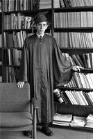 Adolescent boy standing in cap and gown in front of a bookcase