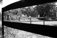 View of fence around paddock at Meadowbrook Stables in Chevy Chase, Maryland with building in background