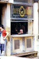 Man sipping coffee by window at Café D'Ouro in Portugal