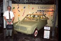 "Man posing in front of ""shootem"" car at Yugo Next exhibition in Union Station, Washington, D.C."