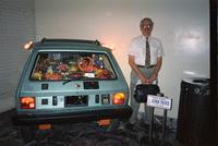 "Man posing in front of ""junkyard"" car at Yugo Next exhibition in Union Station, Washington, D.C."