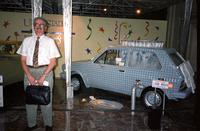 "Man posing in front of ""car wash"" car at Yugo Next exhibition in Union Station, Washington, D.C."