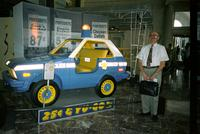 "Man posing in front of ""police"" car at Yugo Next exhibition in Union Station, Washington, D.C."