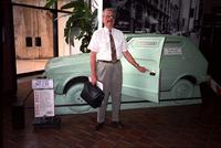 "Man posing in front of ""got 2 go"" car at Yugo Next exhibition in Union Station, Washington, D.C."