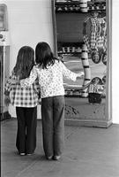 Young girls standing in front of a fun house mirror
