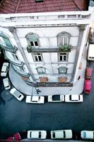 Aerial view displays a person standing by a building and cars parked alongside the sidewalk