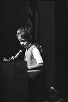Young girl speaking into a microphone at a podium